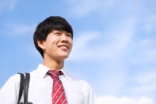青空をバックに立つ男子高校生の写真素材 [FYI02969805]