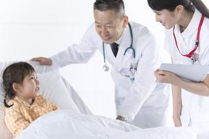 入院患者の女の子を診察する男性医師と女性看護師の写真素材 [FYI02969807]