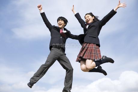 青空をバックにジャンプをする高校生たちの写真素材 [FYI02969811]