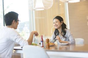 ダイニングテーブルで食事を楽しむ夫婦の写真素材 [FYI02969813]