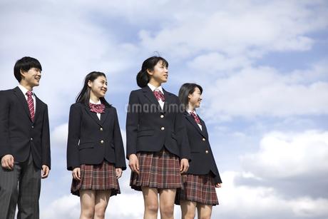 青空をバックに立つ高校生たちの写真素材 [FYI02969814]