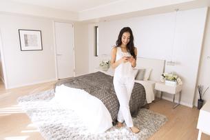 寝室でスマホを見る女性の写真素材 [FYI02969818]