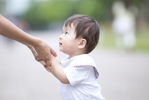 母親の手に掴まって立つ赤ちゃんの写真素材 [FYI02969821]