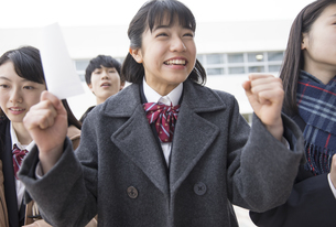 受験番号票を手に合格を喜ぶ女子高校生の写真素材 [FYI02969823]