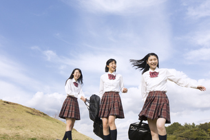 青空をバックに歩く女子高校生たちの写真素材 [FYI02969824]