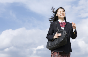 青空をバックに走る女子高校生の写真素材 [FYI02969825]