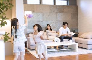 リビングで遊ぶ姉妹を見る母親と本を読む父親の写真素材 [FYI02969837]