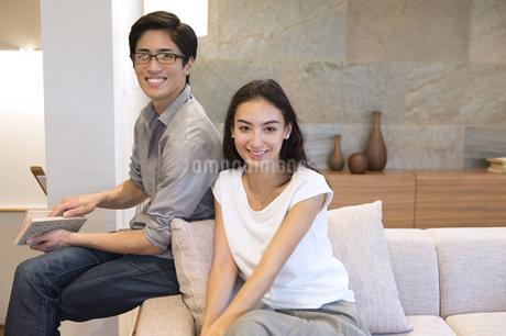 ソファーに座りカメラ目線の夫婦の写真素材 [FYI02969839]