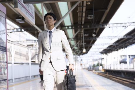 駅のホームを歩くビジネス男性の写真素材 [FYI02969844]