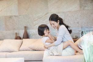 ソファーで戯れる母親と娘の写真素材 [FYI02969852]