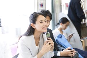 電車の座席に座り笑顔のビジネス女性の写真素材 [FYI02969853]