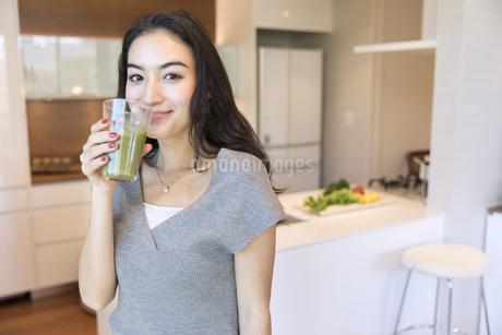 スムージーを持ちカメラ目線の女性の写真素材 [FYI02969874]