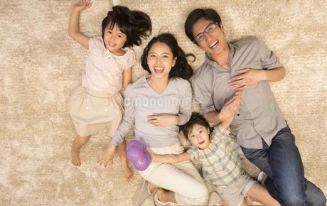 床に寝転がりカメラ目線の家族の写真素材 [FYI02969877]