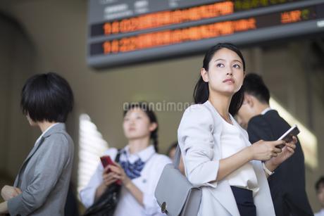 駅のホームでスマホを持ち遠くを見るビジネス女性の写真素材 [FYI02969879]