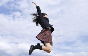 青空をバックにジャンプをする女子高校生の写真素材 [FYI02969881]