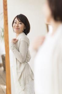 鏡の前で洋服を合わせる女性の写真素材 [FYI02969882]