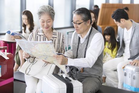 地図を見て話すシニア夫婦の写真素材 [FYI02969883]