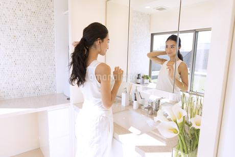 鏡の前で髪を整える女性の写真素材 [FYI02969887]