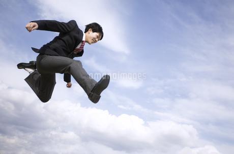 青空をバックにジャンプをする男子高校生の写真素材 [FYI02969891]