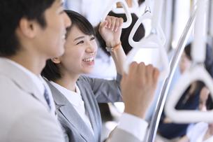 電車で男性と会話をするビジネス女性の写真素材 [FYI02969896]
