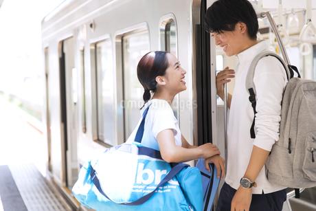 電車の入り口で会話をする男女の写真素材 [FYI02969898]