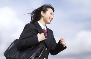 青空をバックに走る女子高校生の写真素材 [FYI02969907]