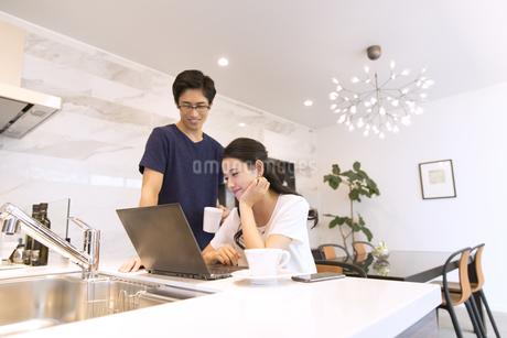 キッチンでパソコンを見る夫婦の写真素材 [FYI02969908]