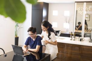 ダイニングでパソコンを見る夫婦の写真素材 [FYI02969916]