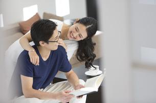 本を読む夫の背に抱きつく妻の写真素材 [FYI02969920]
