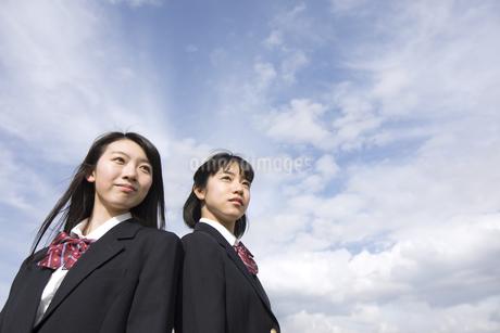 青空をバックに背中合わせで立つ女子高校生たちの写真素材 [FYI02969925]