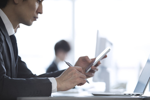 スマートフォンを操作するビジネス男性の写真素材 [FYI02969928]