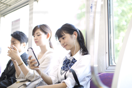 電車で音楽を聴きながらスマホを操作する女子高校生の写真素材 [FYI02969930]
