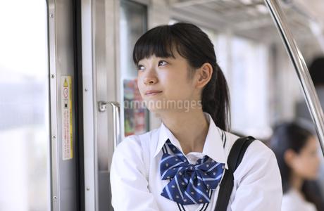 電車で外の景色を見つめる女子高校生の写真素材 [FYI02969931]