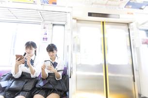 電車に乗る女子高校生たちの写真素材 [FYI02969934]
