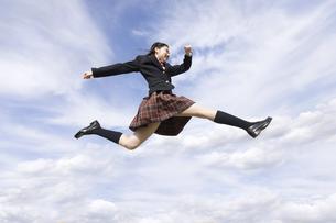 青空をバックにジャンプをする女子高校生の写真素材 [FYI02969937]