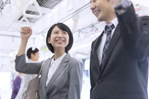 電車で男性と会話をするビジネス女性の写真素材 [FYI02969939]