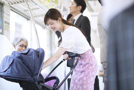 電車の中で赤ちゃんをあやす母親の写真素材 [FYI02969940]