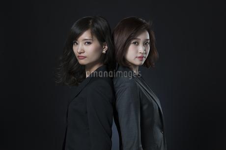 背中を合わせるビジネス女性2人の写真素材 [FYI02969952]