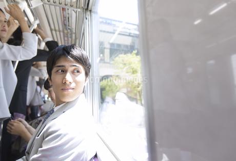 電車の座席に座り外を見つめるビジネス男性の写真素材 [FYI02969955]