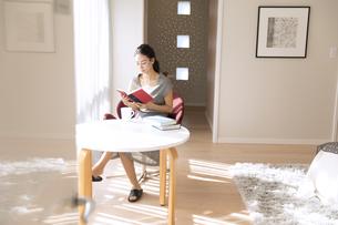 椅子に座り本を読む女性の写真素材 [FYI02969956]