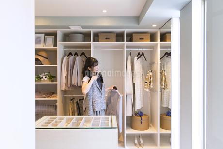 ウォークインクローゼットで服を選ぶ女性の写真素材 [FYI02969961]