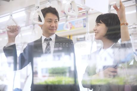 電車で会話をするビジネス男女の写真素材 [FYI02969965]