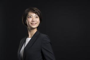 上を見上げ微笑むビジネス女性の写真素材 [FYI02969967]