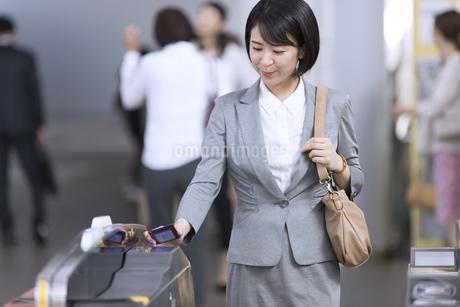 駅の改札に定期券をかざすビジネス女性の写真素材 [FYI02969970]
