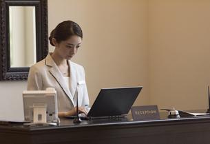 フロントでパソコンを操作する女性スタッフの写真素材 [FYI02969973]