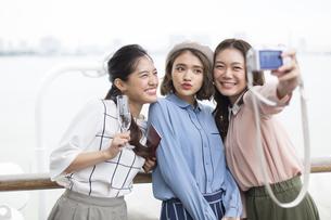 シャンパンを持ち自撮りをする3人の女性の写真素材 [FYI02969975]