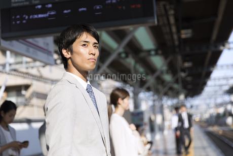 駅のホームで電車を待つビジネス男性の写真素材 [FYI02969976]