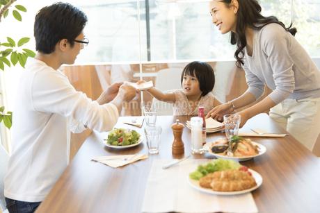 ダイニングテーブルで食事を楽しむ家族の写真素材 [FYI02969977]