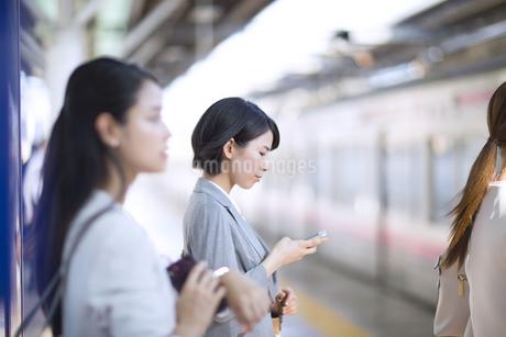 駅のホームでスマホを操作するビジネス女性の写真素材 [FYI02969980]