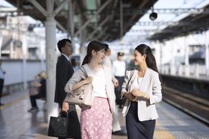 駅のホームで会話をしながら歩くビジネス女性たちの写真素材 [FYI02969982]